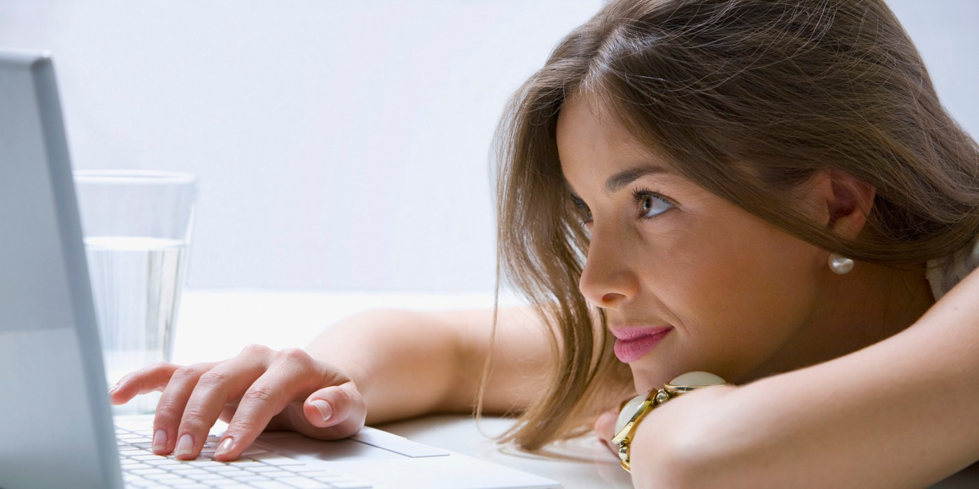 Mixed race businesswoman laying on desk using laptop